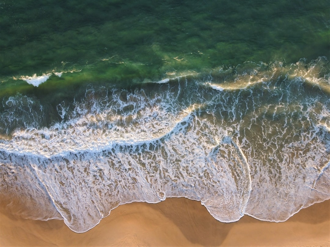 Aerial view of waves breaking onto the beach at sunrise