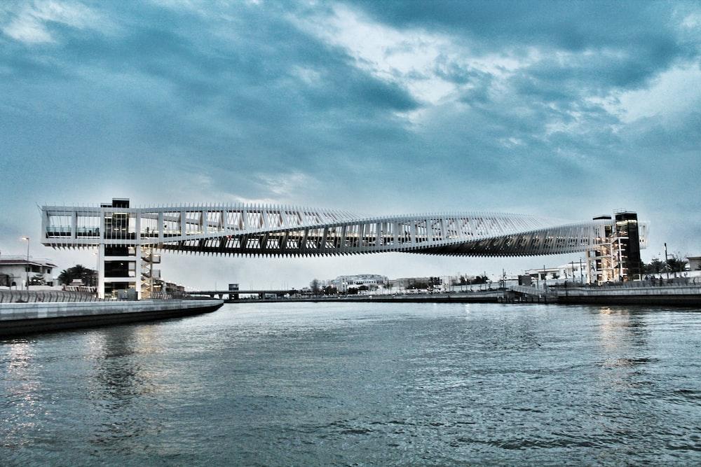 white boat on water under bridge during daytime