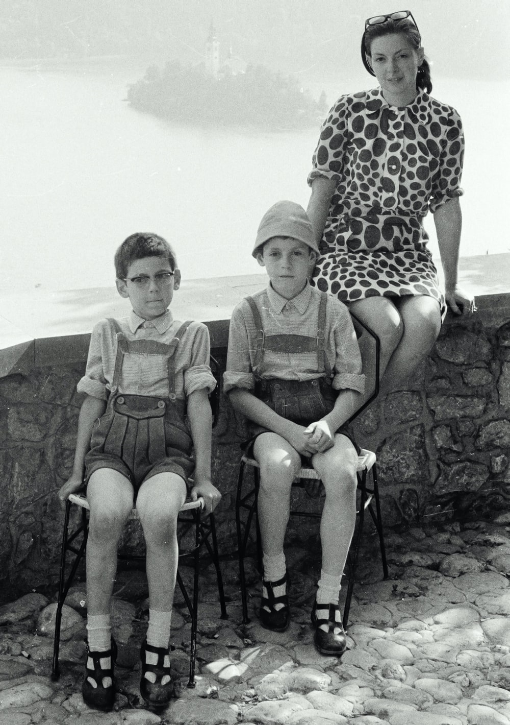 grayscale photo of 2 women sitting on rock