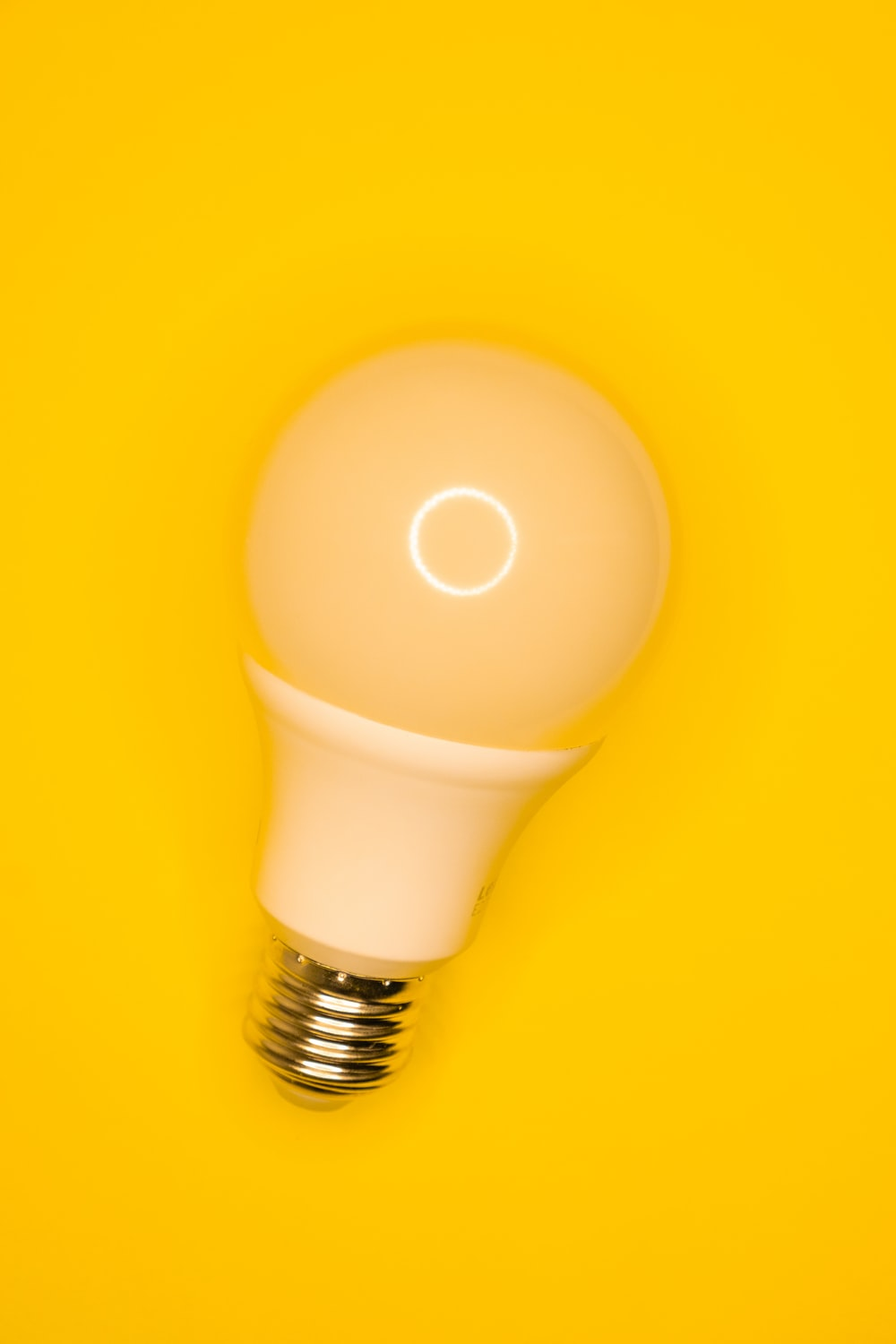 white light bulb on yellow surface