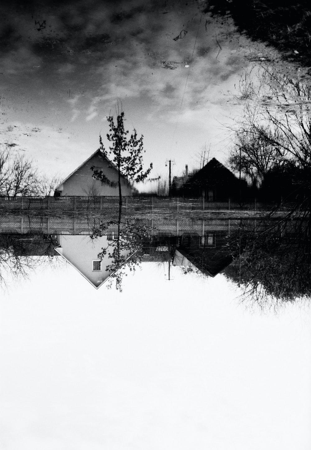 grayscale photo of house near lake