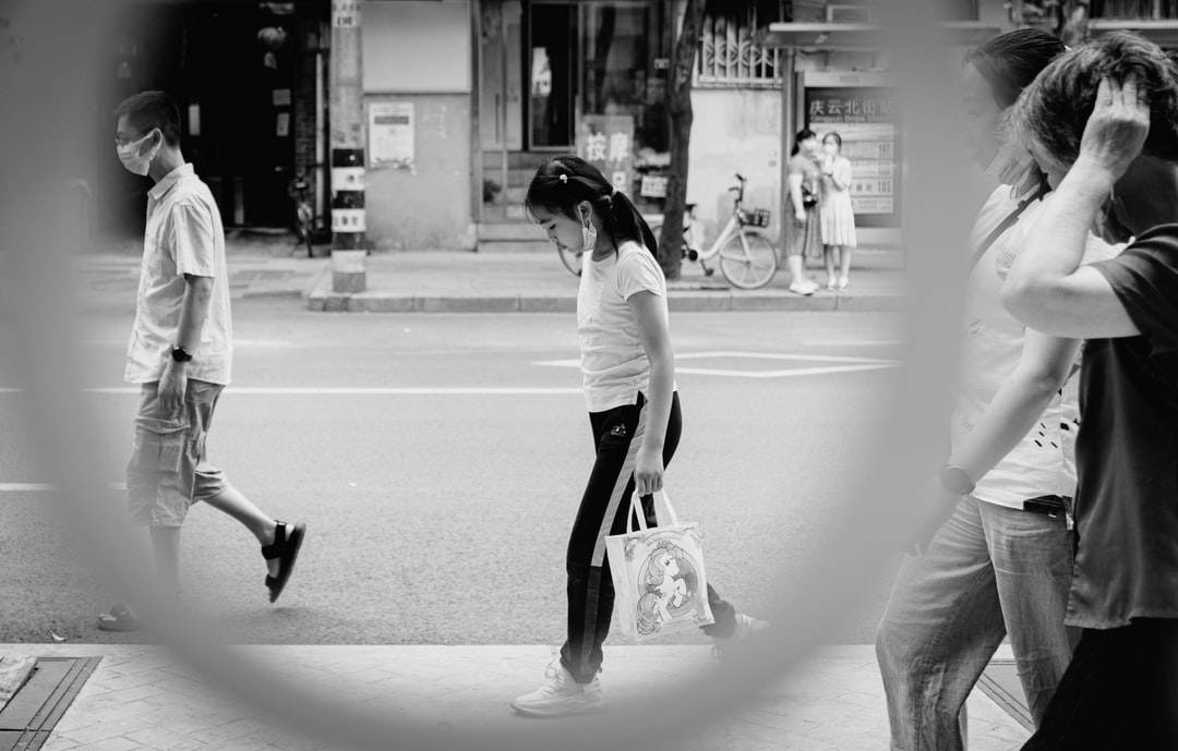 Woman In White Long Sleeve Shirt and Black Pants Walking On Street - unsplash