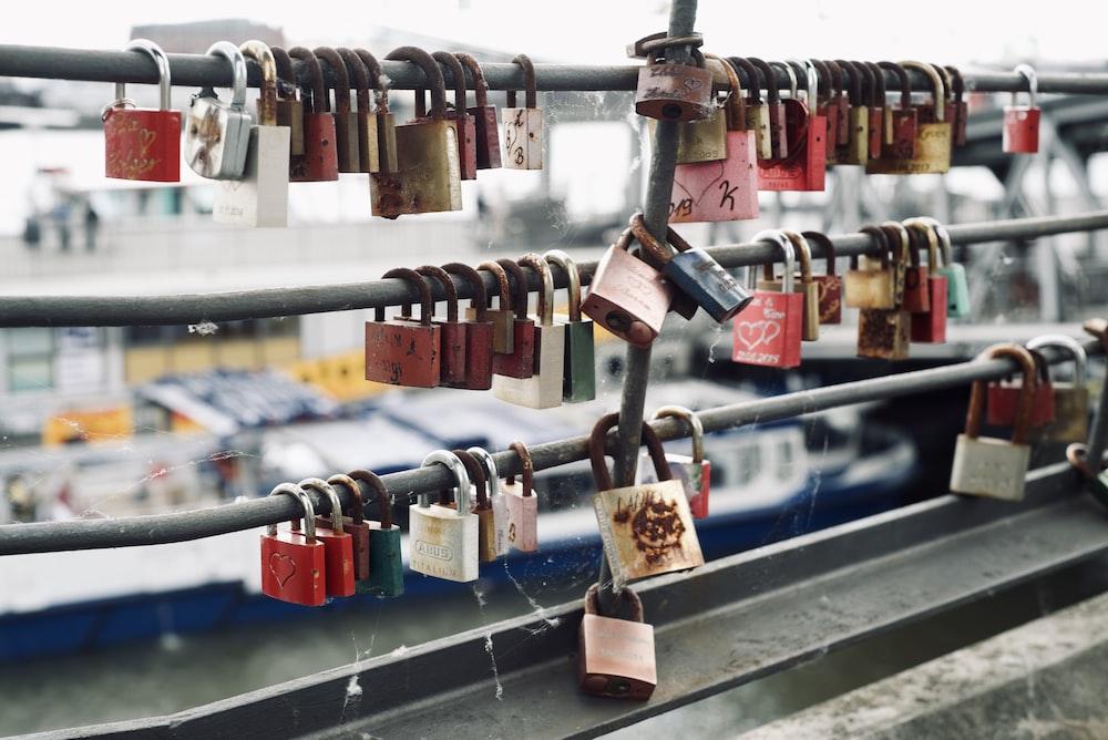 padlocks on metal fence during daytime
