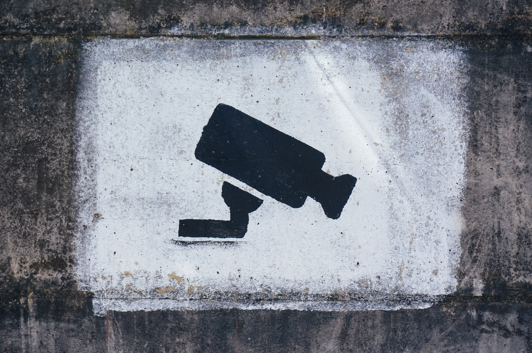 A surveillance camera painted to a building to show the issues with surveillance when it comes to your cybersecurity.