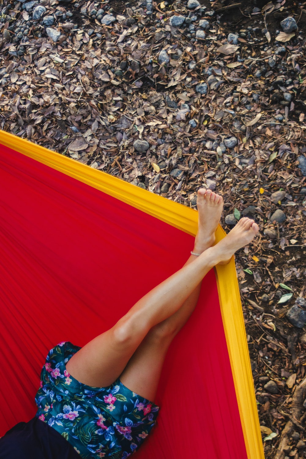 woman in red dress lying on yellow and red hammock