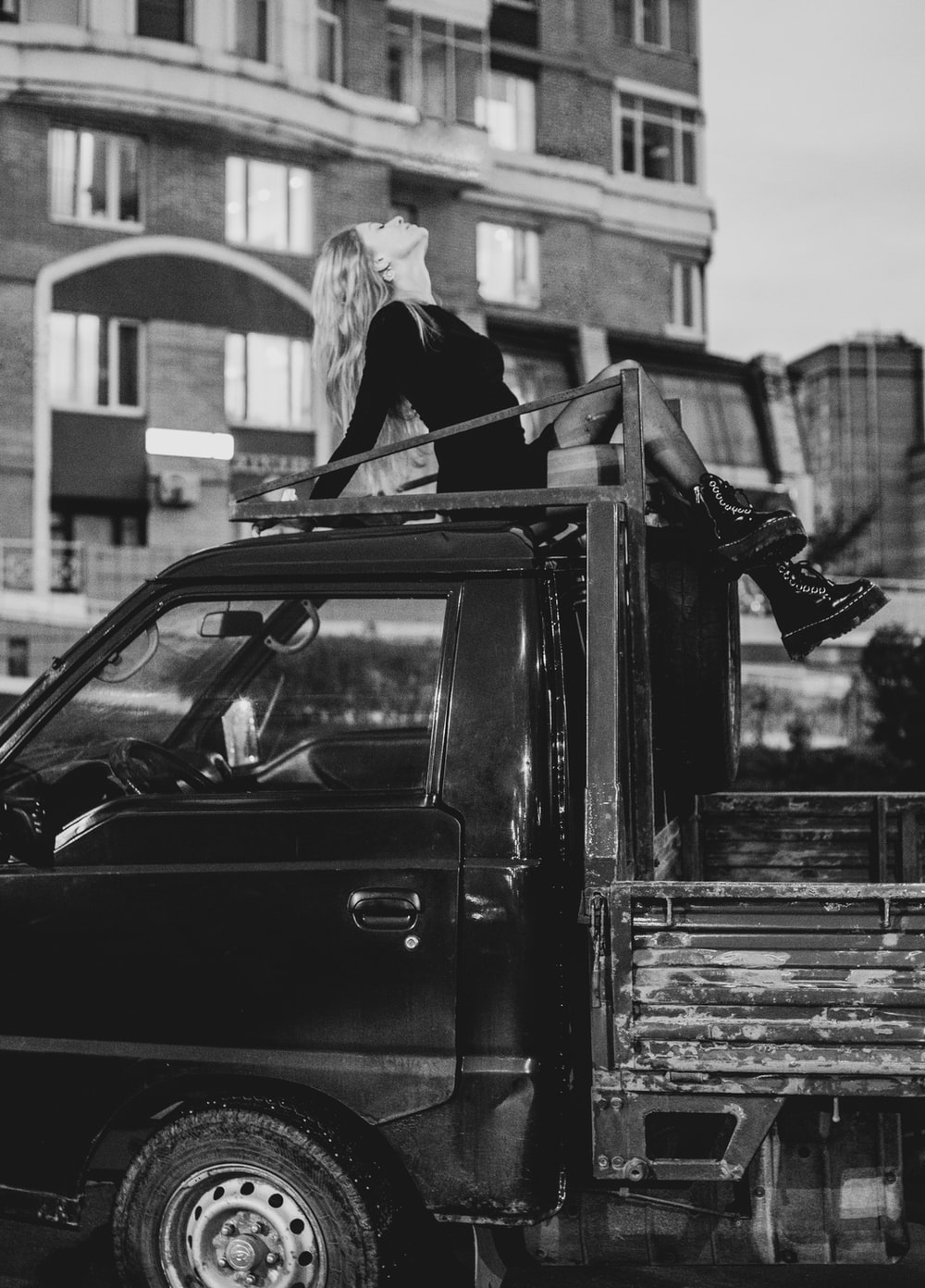 grayscale photo of woman in black jacket and white knit cap standing beside car
