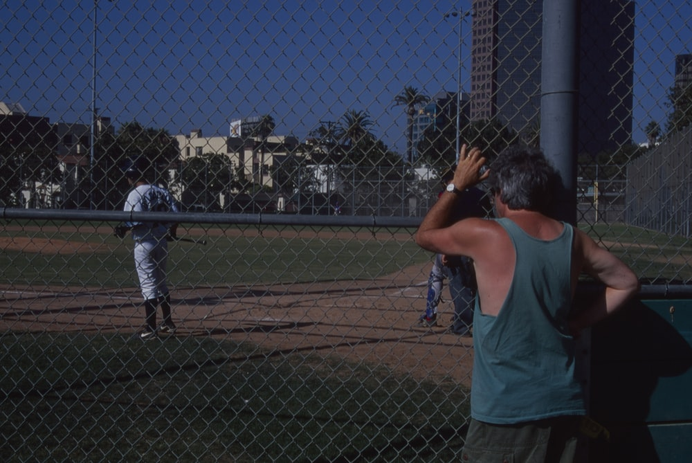 woman in blue tank top and white pants holding baseball bat during daytime
