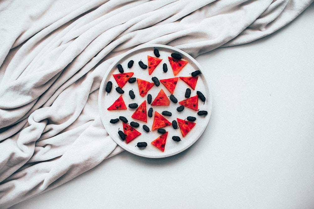 red and white round ceramic bowl on white textile