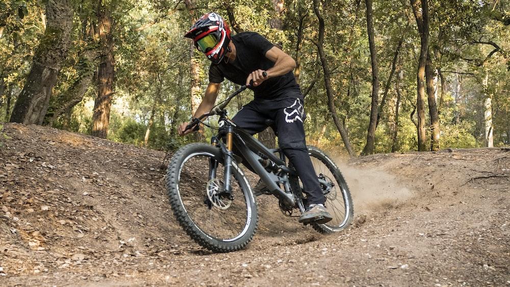 man in black shirt riding on black mountain bike