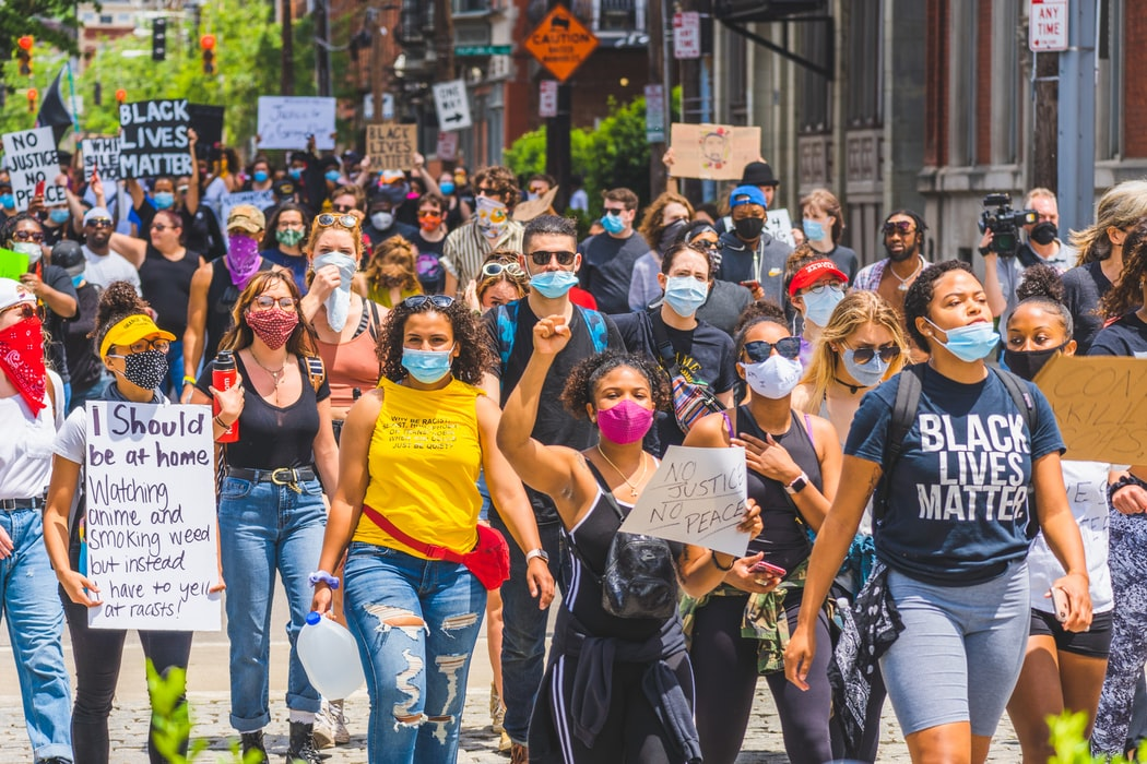 "A photo of a Black Lives Matter protest in summer of 2020. There is a large crowd of people holding signs like ""Black Lives Matter"" and ""no justice no peace"", most of them are also wearing medical or homemade face coverings to protect the crowd from COVID"