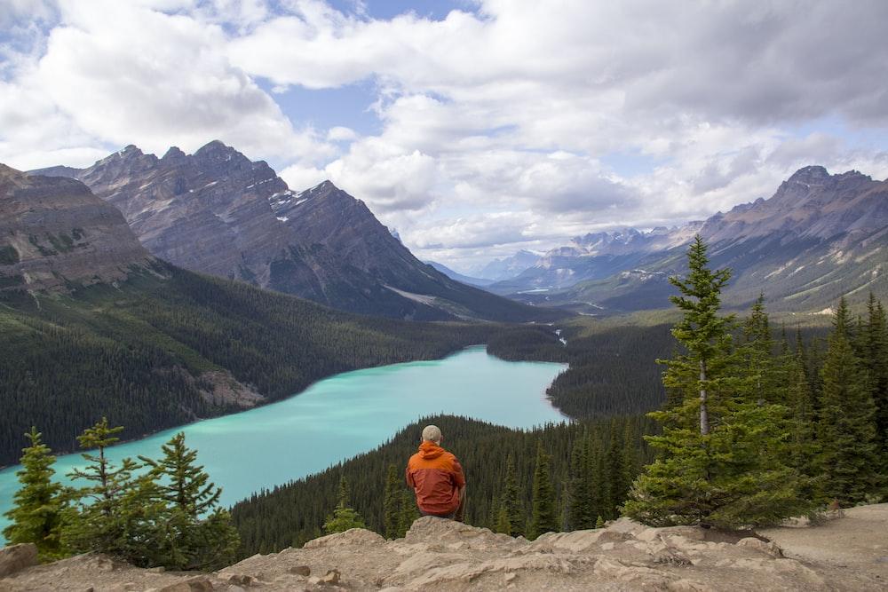 person in orange hoodie sitting on rock near lake during daytime
