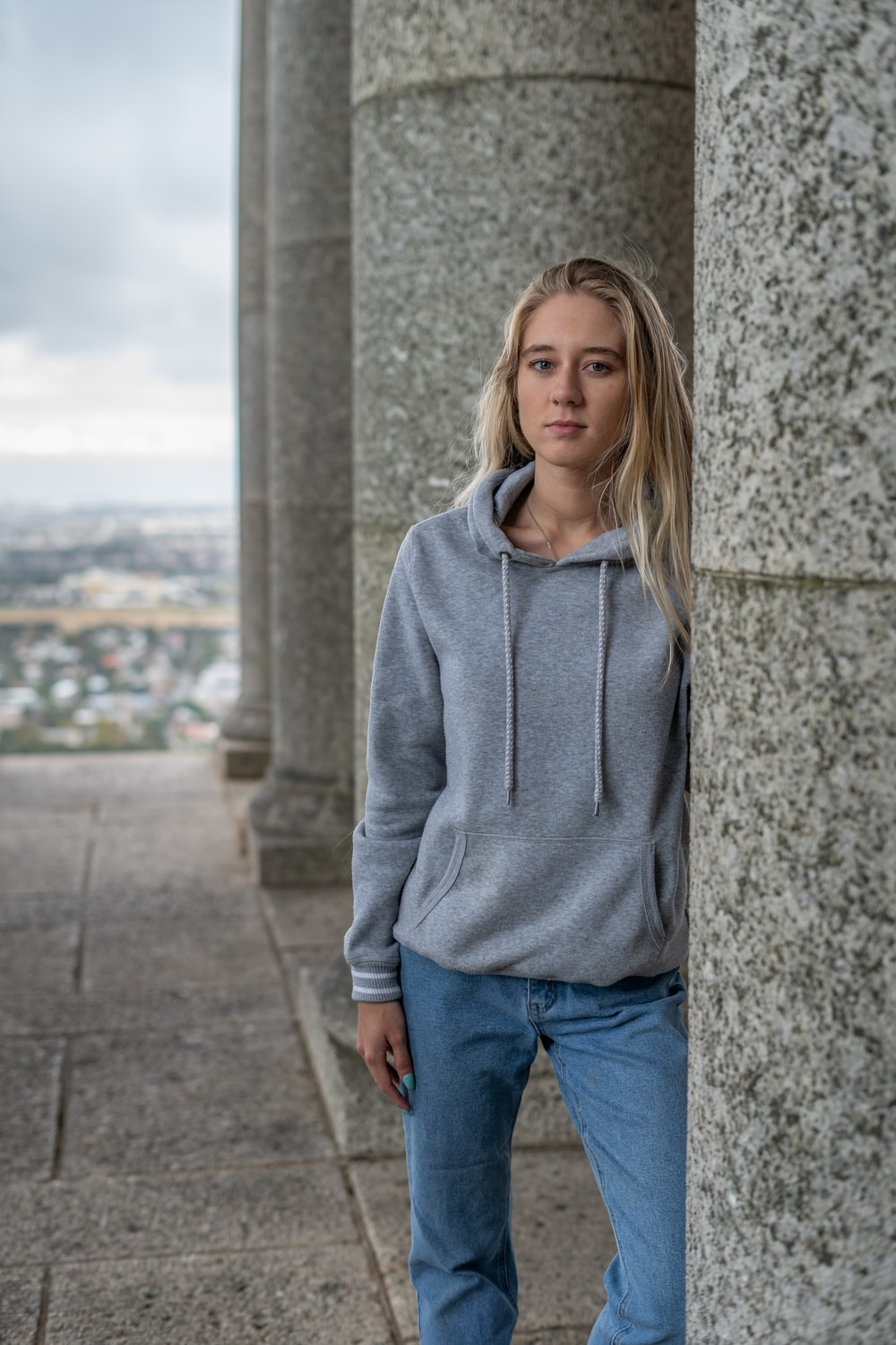 woman in gray hoodie standing beside gray concrete wall during daytime