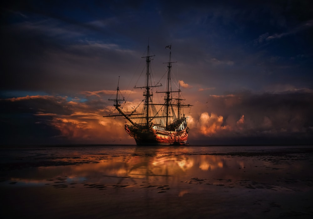 brown ship on sea during sunset