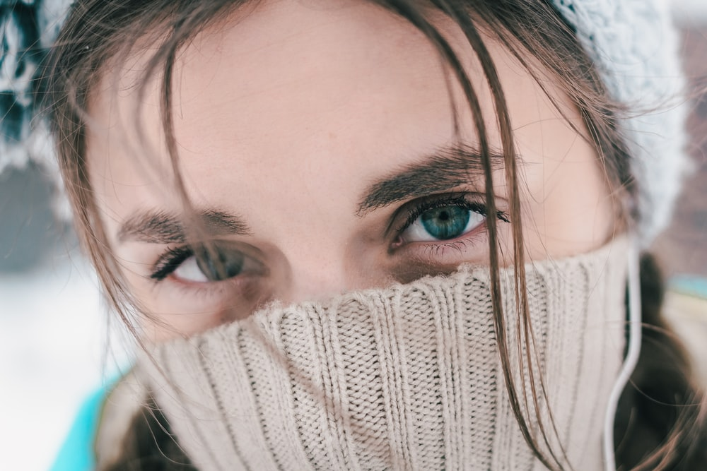 woman with brown hair covering her face with white knit textile