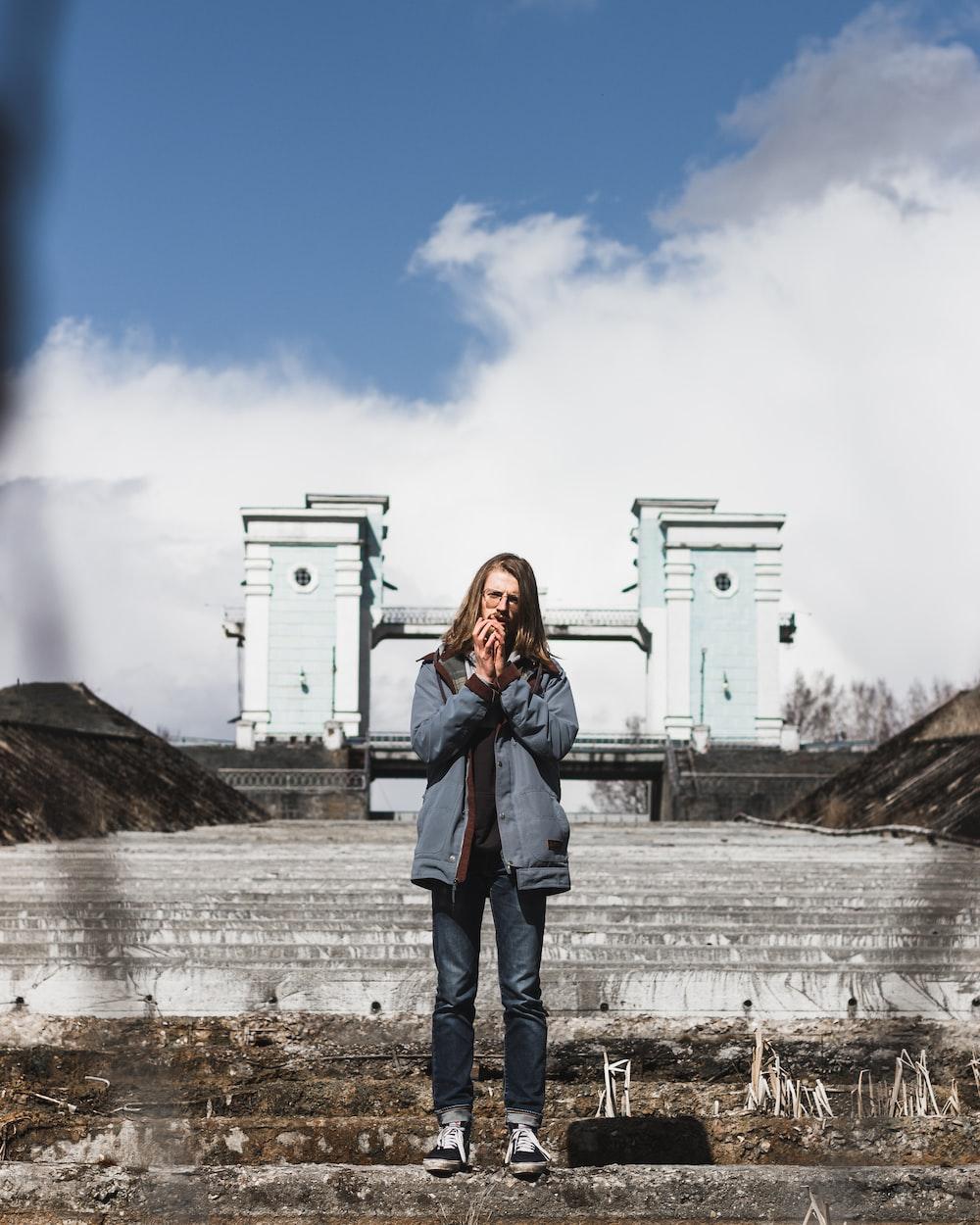 woman in blue denim jacket standing near white building