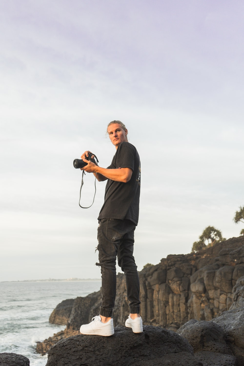 man in black t-shirt and gray pants holding camera standing on rock formation near sea