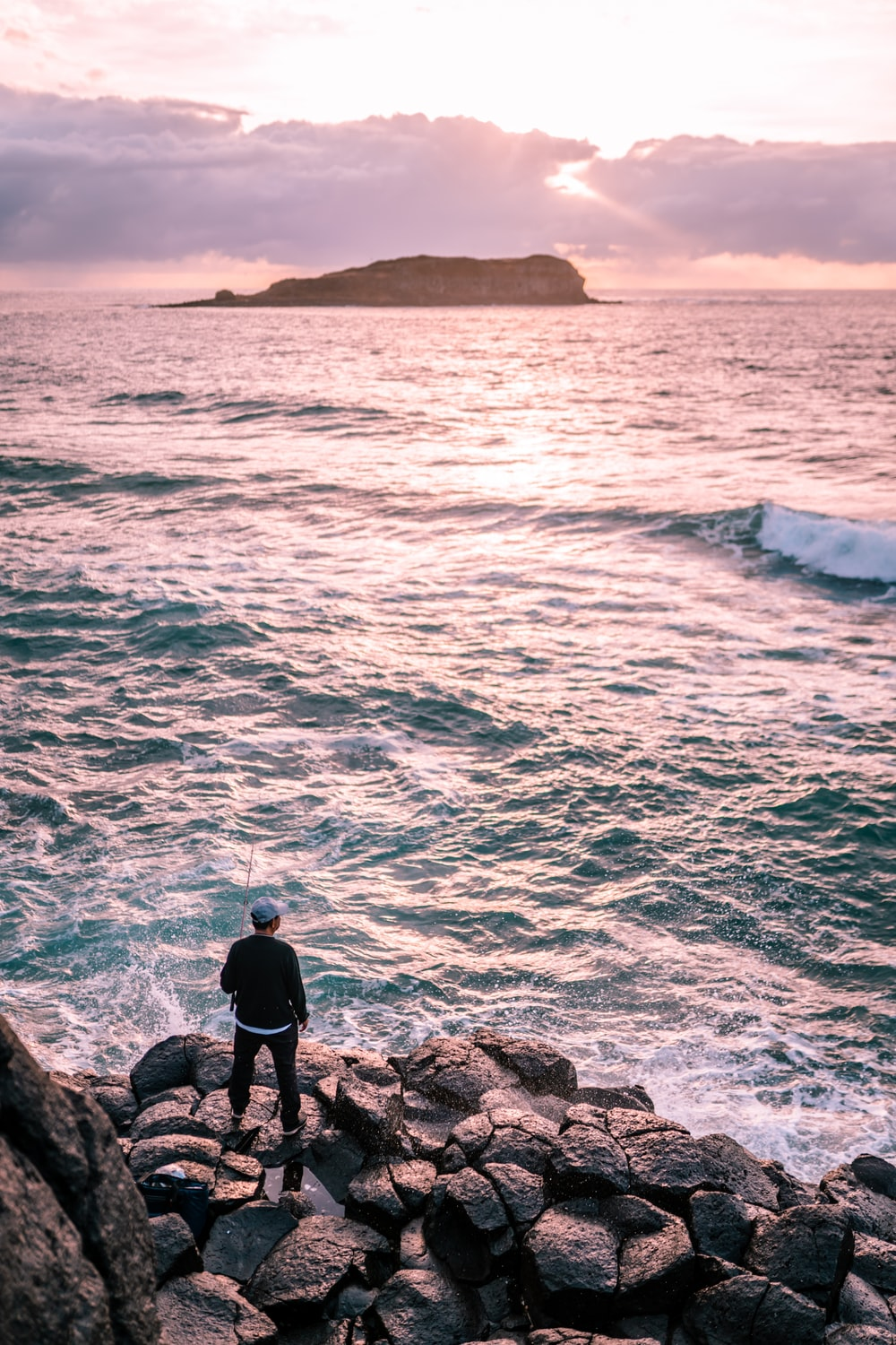 man in black jacket standing on rock formation near body of water during daytime