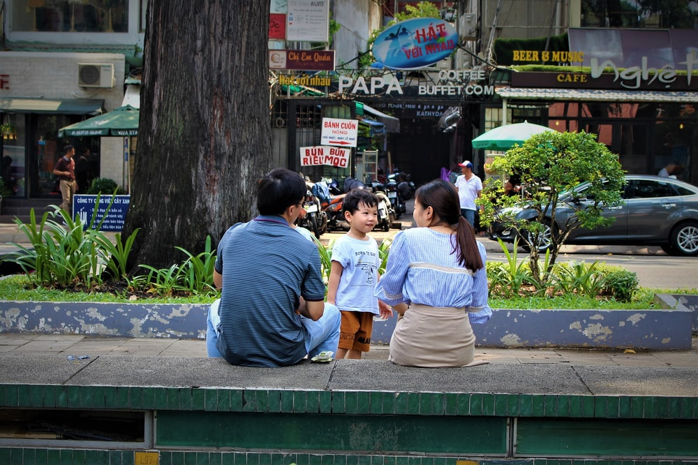 people sitting on bench near road during daytime