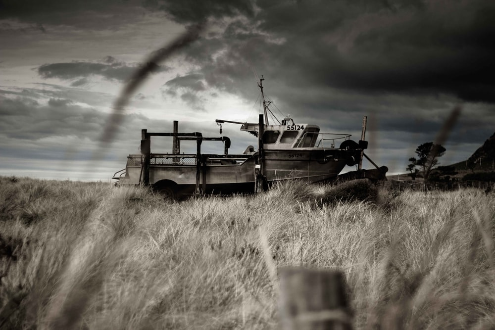 black and white utility trailer on brown grass field under cloudy sky during daytime