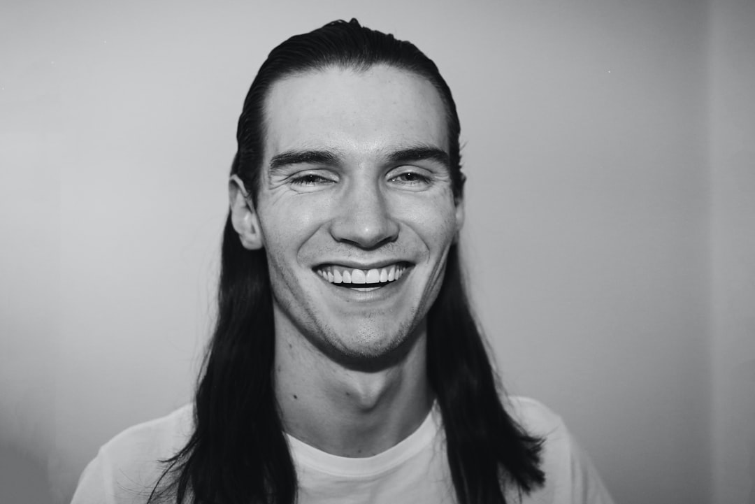 Smiling man laughing. Man with long hair.