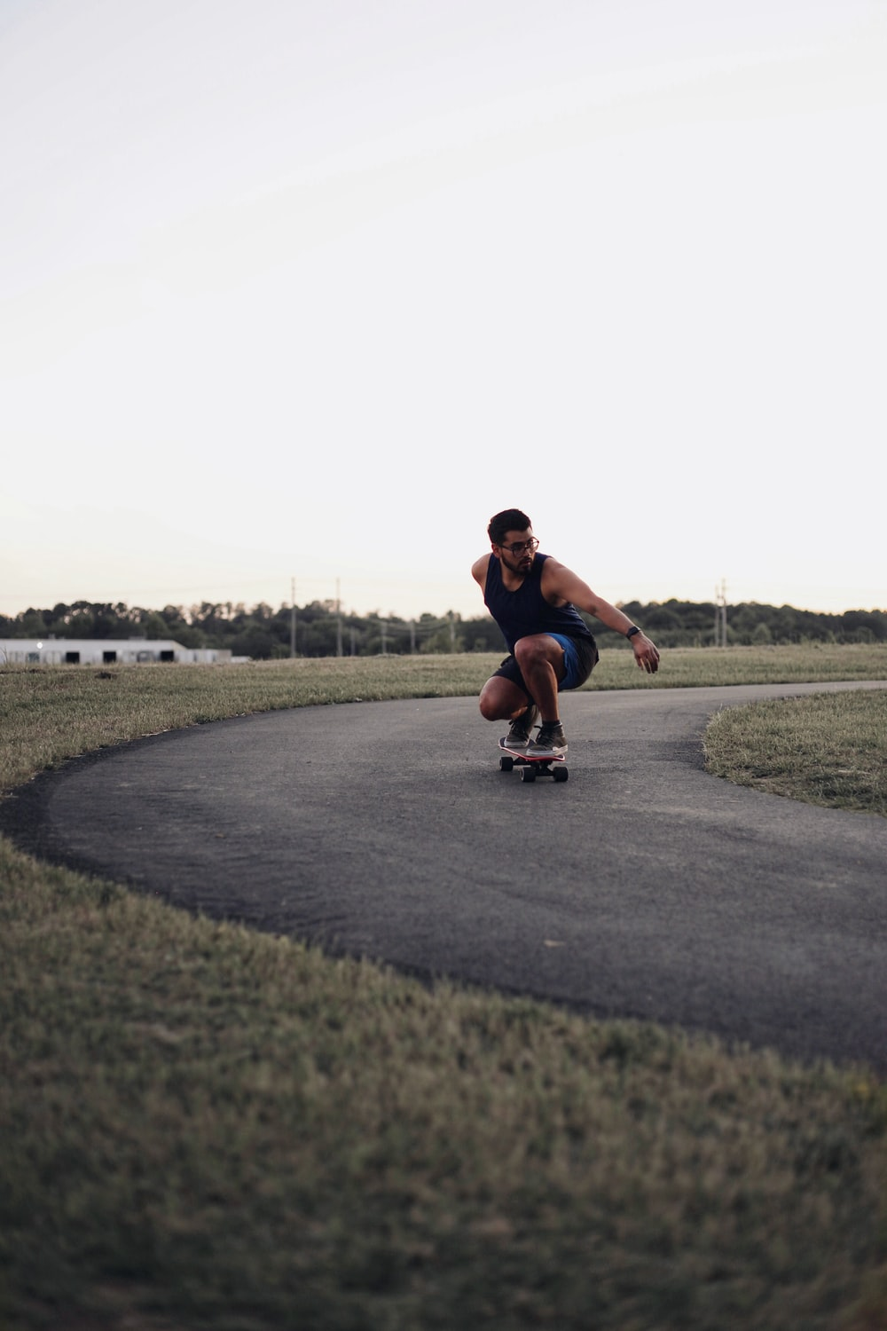 man in red t-shirt and black shorts riding skateboard during daytime
