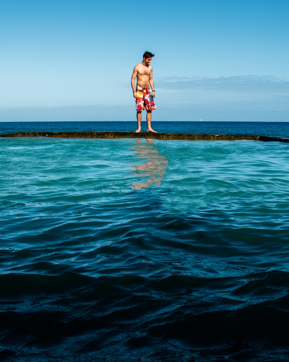 man in blue shorts standing on rock in the middle of sea during daytime