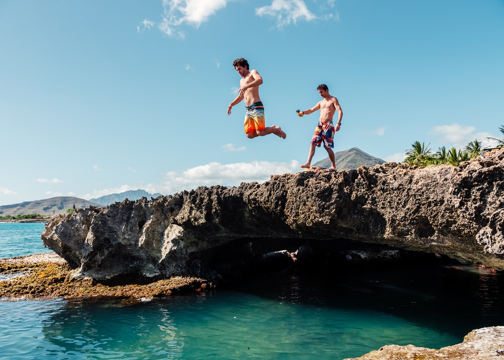 2 boys jumping on rocky mountain during daytime
