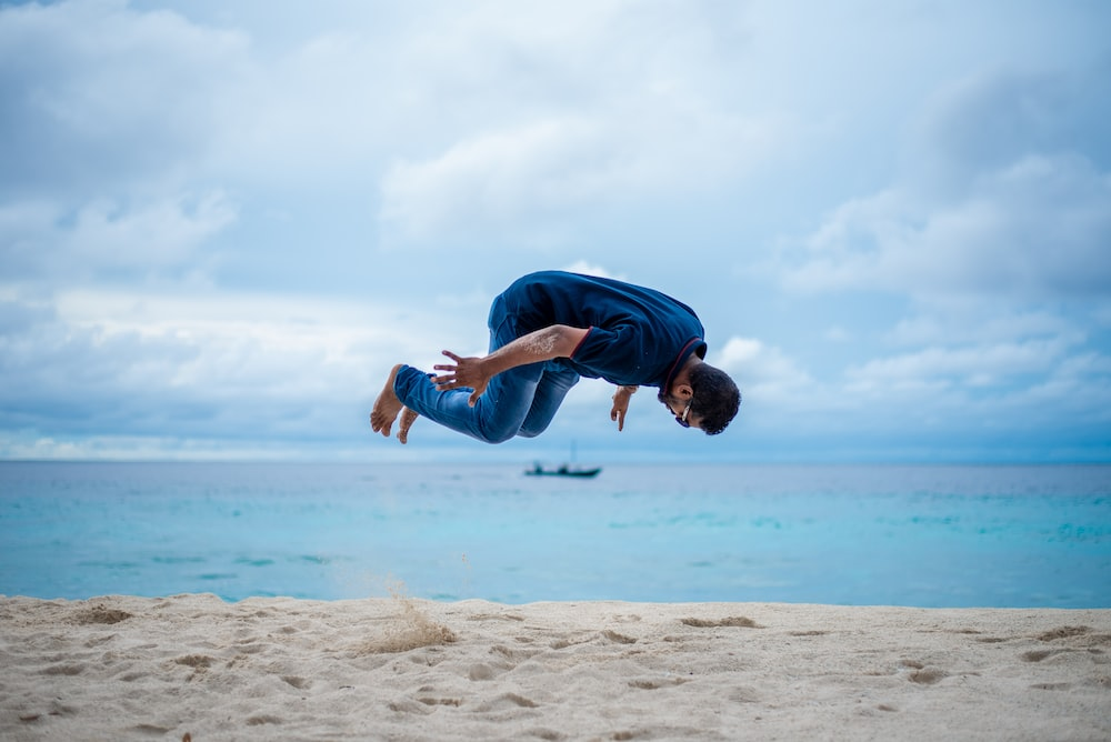 man in blue t-shirt and blue denim jeans jumping on beach during daytime