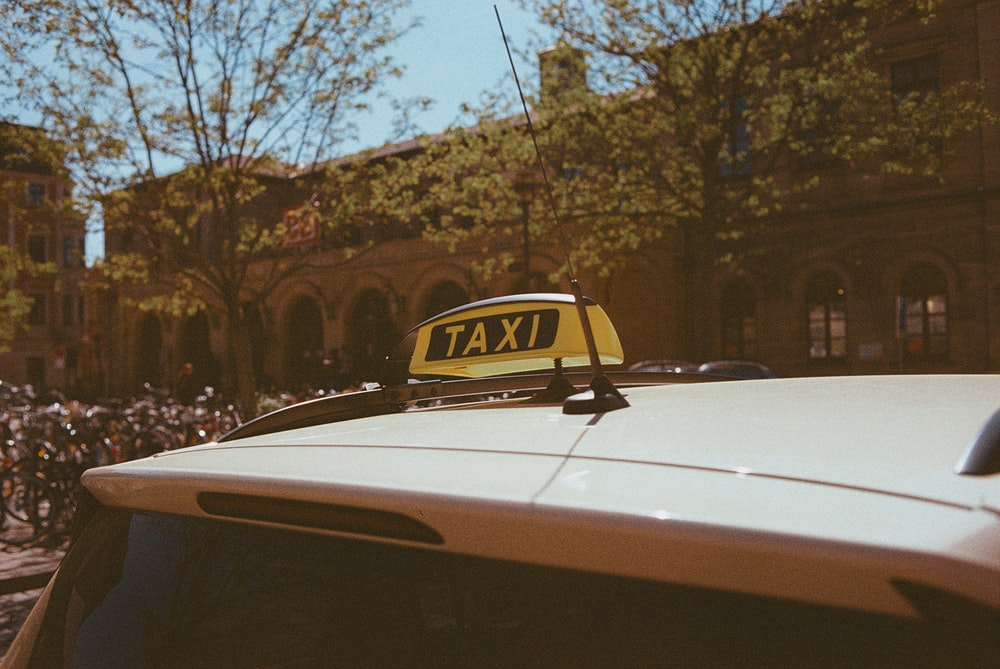 yellow taxi cab on road during daytime
