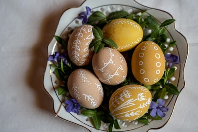 three brown eggs on white ceramic plate easter egg teams background