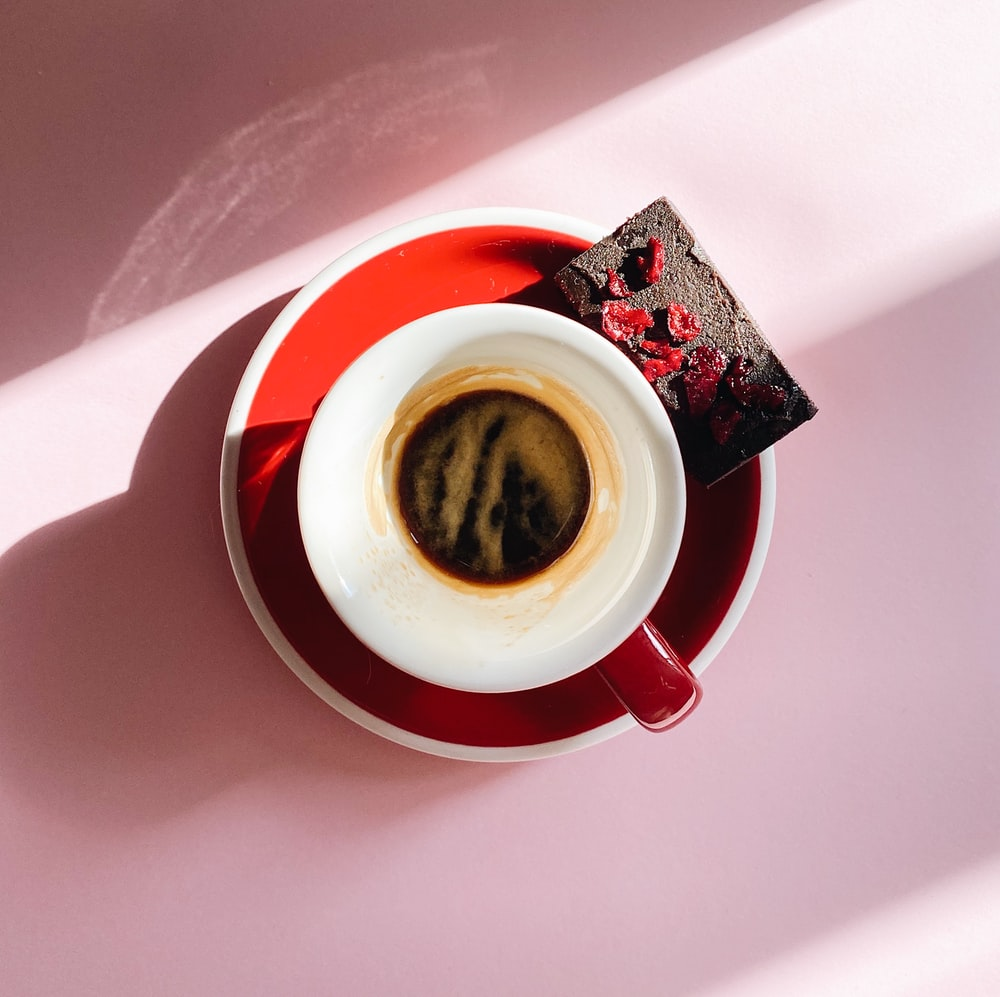 white and red ceramic mug with coffee