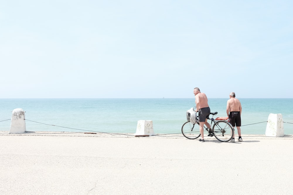 man and woman riding bicycle on beach during daytime