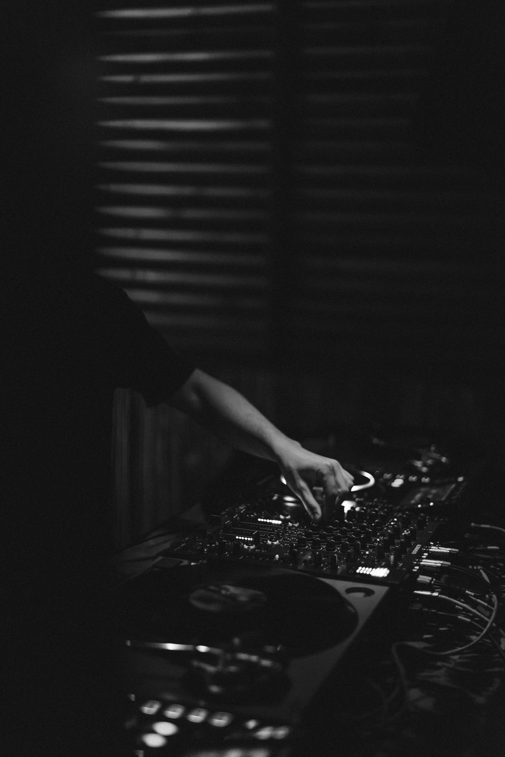 grayscale photo of person playing dj controller