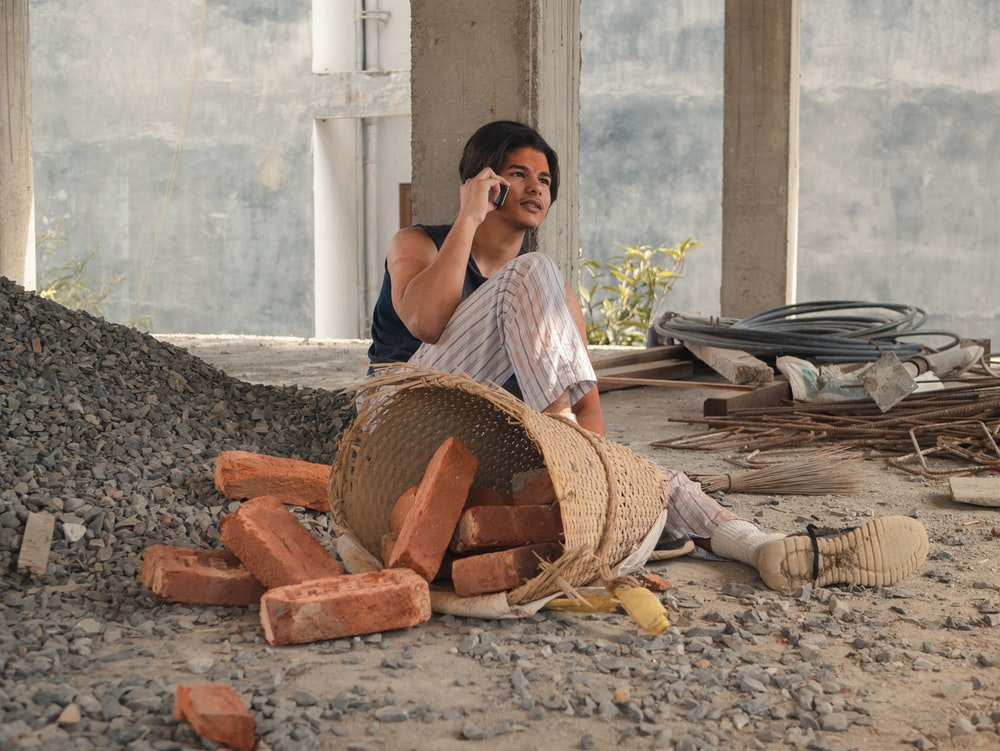 woman in white shirt sitting on ground with brown woven basket