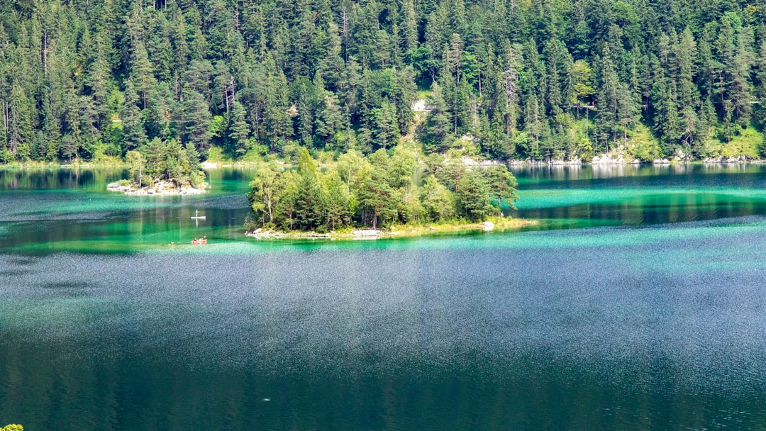 """Island in the lake """"Eibsee"""" with different green and blue colours surrounded by forests."""