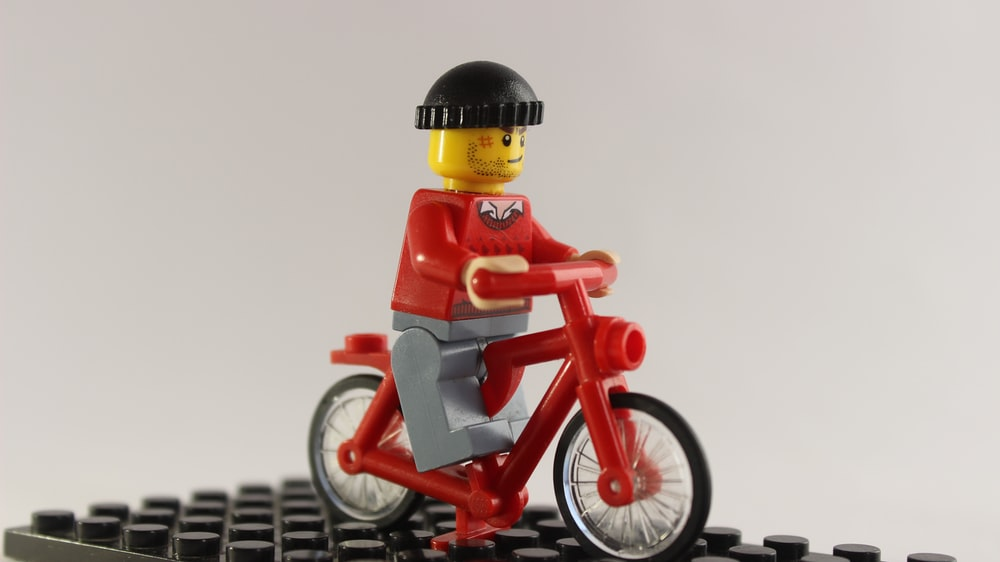 lego minifig riding red and white bicycle