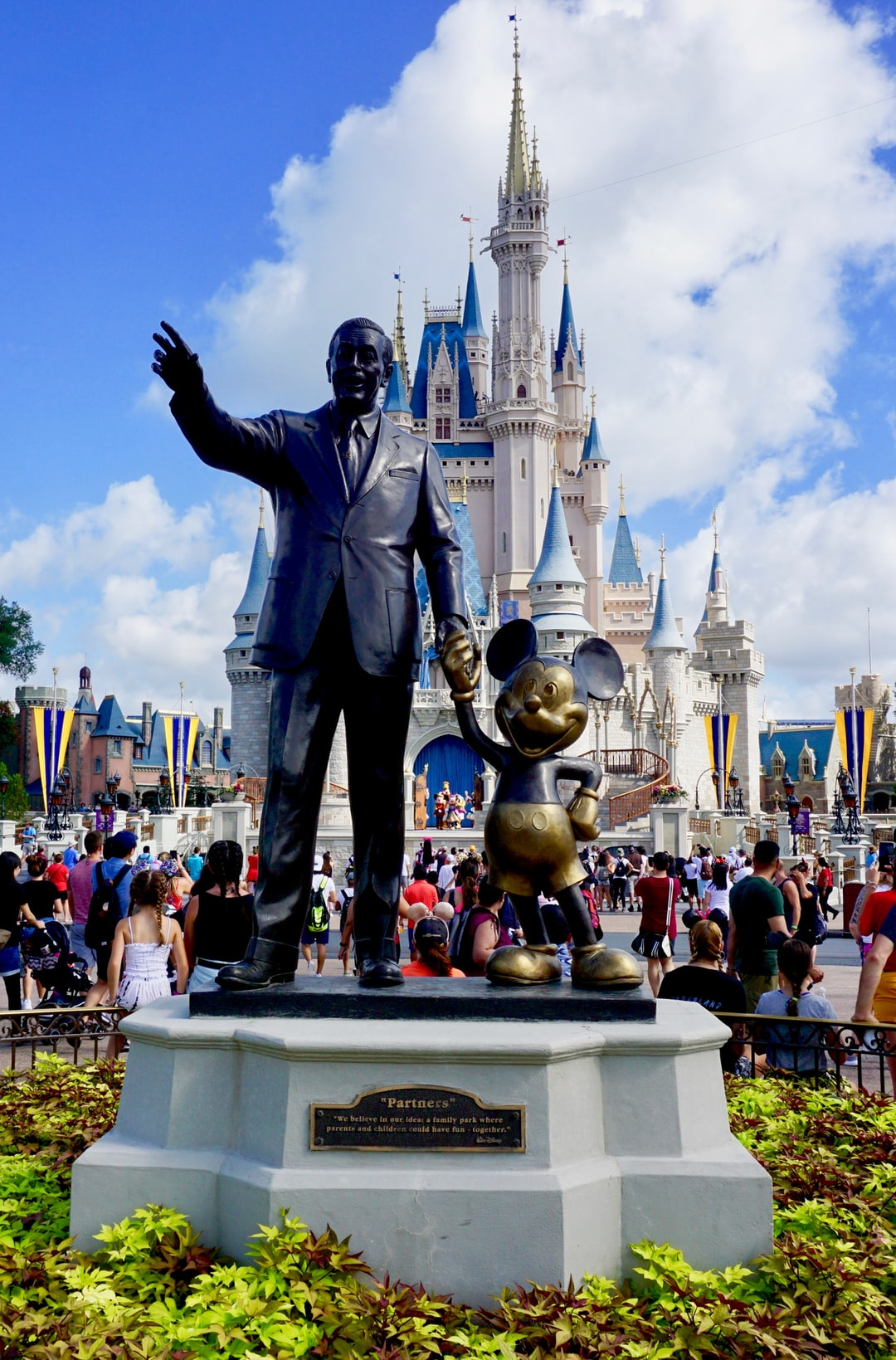 """""""I only hope we never lose sight of one thing ... that it was all started by a mouse"""" - Walt Disney. Statue of Mickey Mouse and Walt Disney at Orlando Magic Kingdom theme park. Behind, the famous Disney castle."""