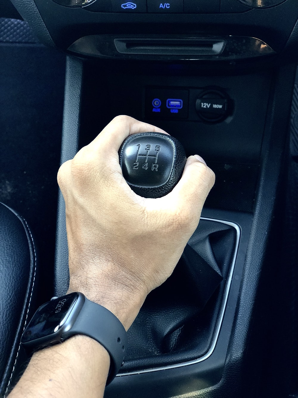 person holding black car gear shift lever