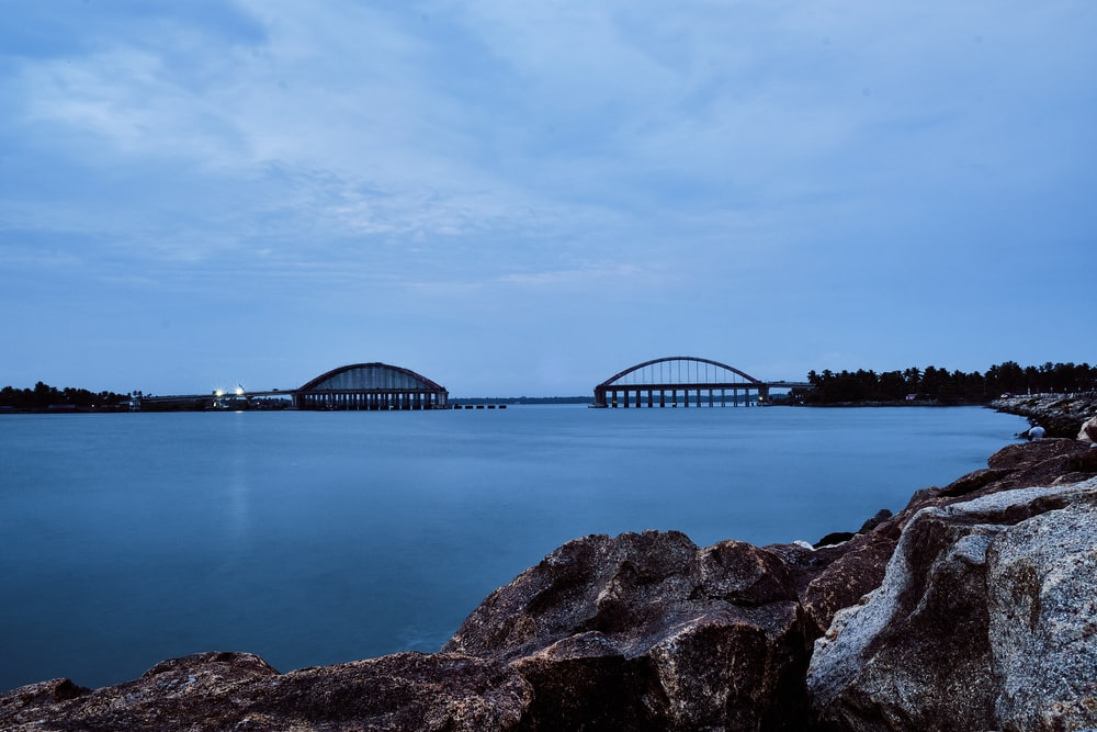 bridge over the water under cloudy sky
