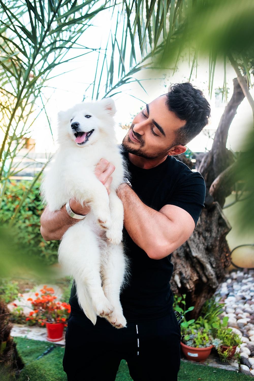 man in black crew neck t-shirt holding white puppy