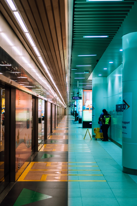 man in black jacket and black pants walking on hallway