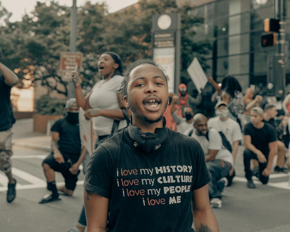 man in black crew neck t-shirt standing on street during daytime
