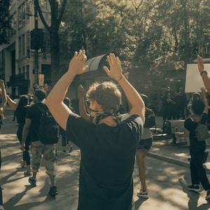 man in black t-shirt and black pants raising his hands