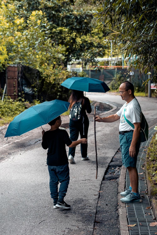 man in black t-shirt holding umbrella while walking on street during daytime