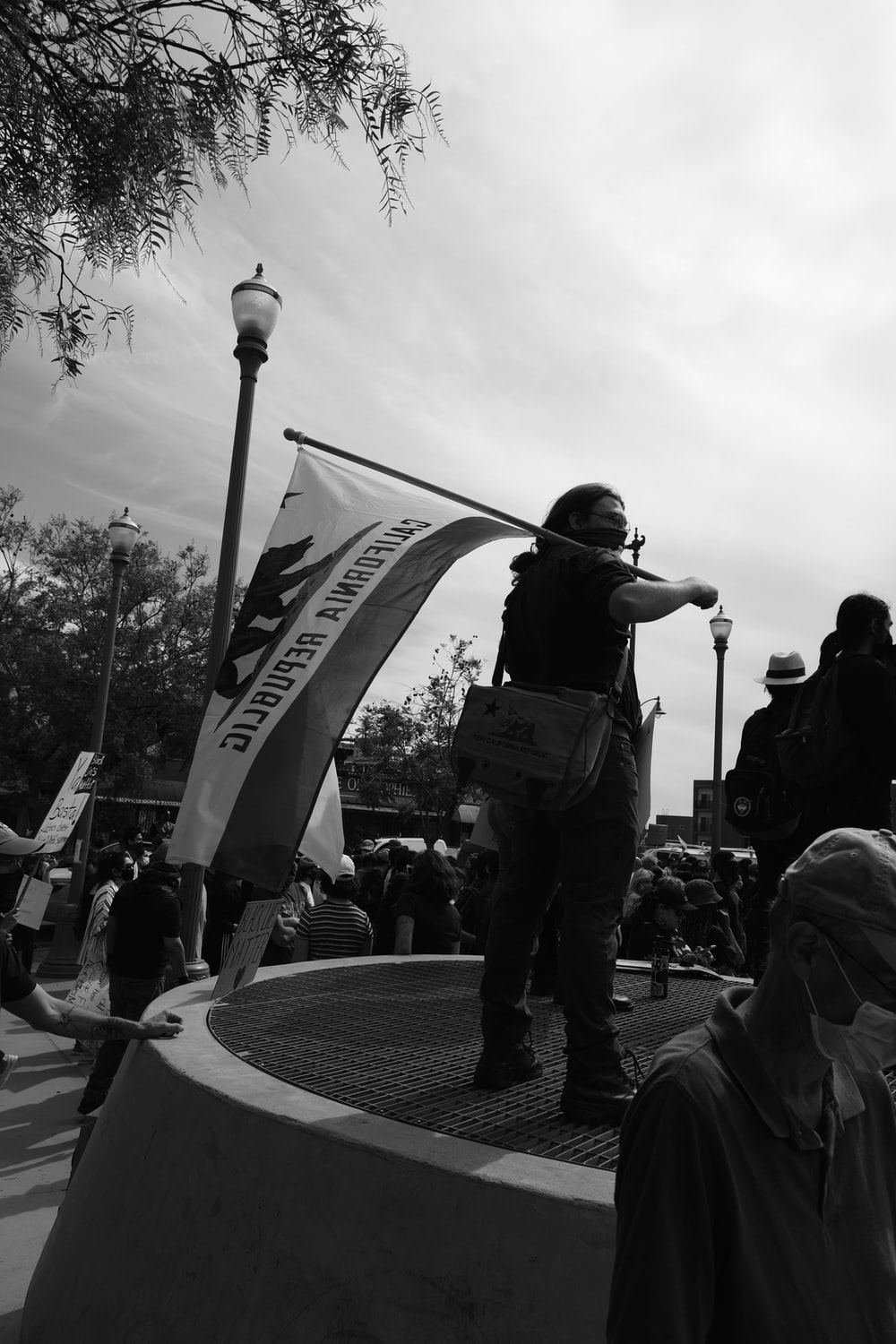 grayscale photo of man in black jacket and pants holding flag