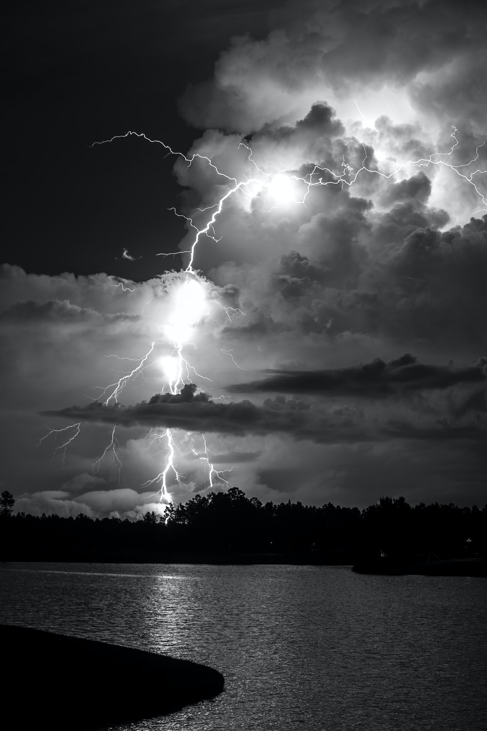 grayscale photo of lightning over body of water
