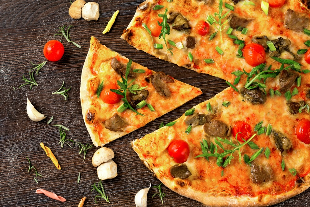 pizza with tomato and green leaves on white ceramic plate