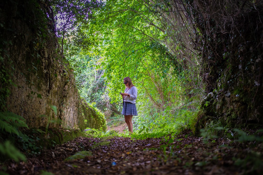 woman in white shirt and blue skirt walking on pathway between green trees during daytime