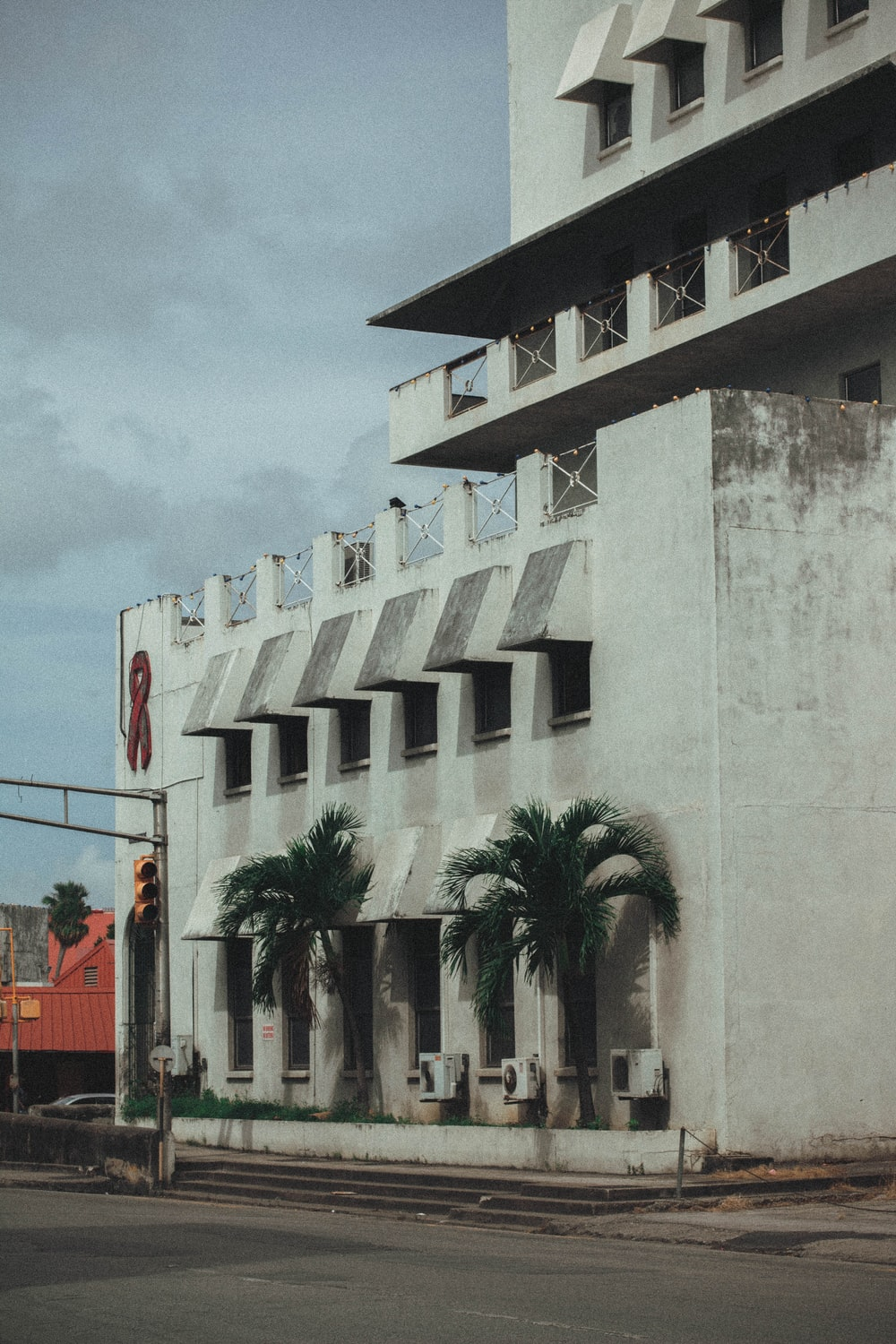 white concrete building near palm trees during daytime