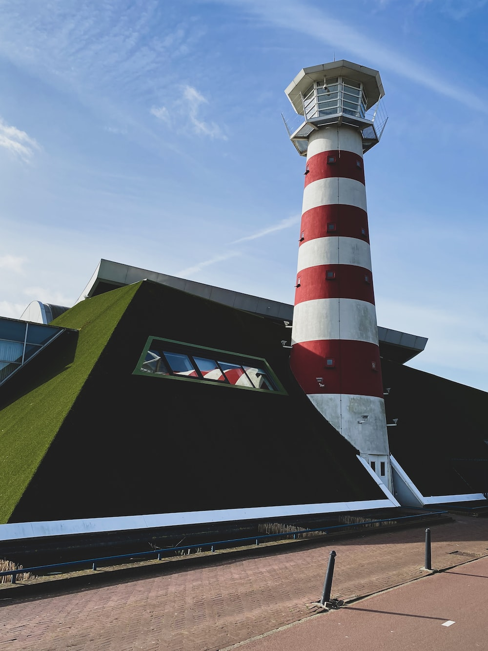 red and white striped lighthouse under blue sky